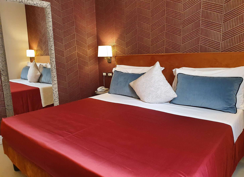 deluxe double_0000_letto con lenzuola rosso cuscino specchio duomo signoria firenze